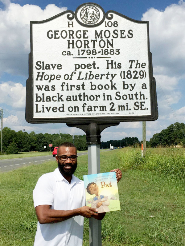 Holding my book about George Moses Horton alongside of the highway marker that honors him.